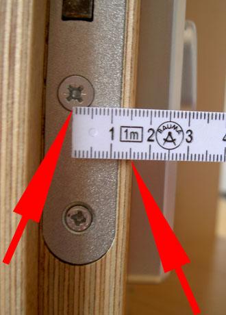Mida desde la mitad del cilindro hasta la esquina de la puerta.
